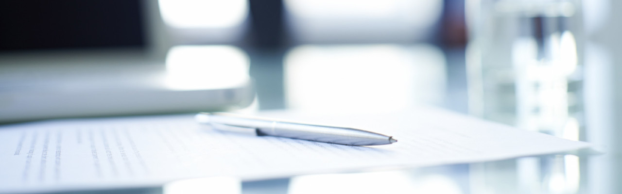 Silver pen and business contract situated on office desk, people in the background